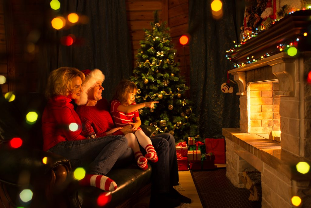 Happy family sitting by fireplace at Christmas tree.  Child shows on fire.